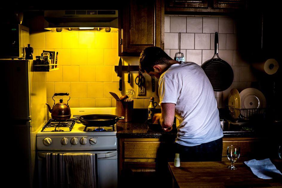 Dečko priprema hranu u kuhinji