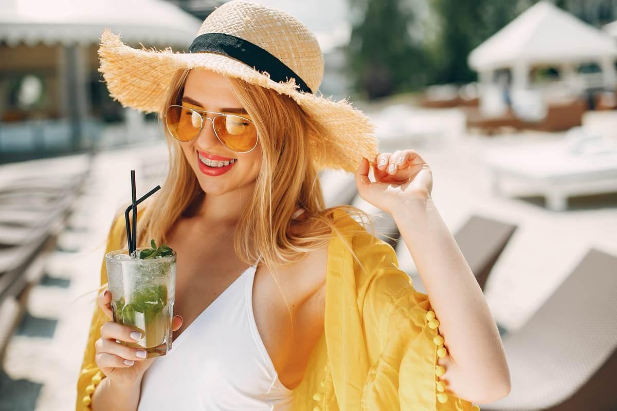 Devojka sa šeširom pije koktel