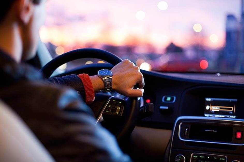 Fotografija sa zadnjeg sedišta muškarca kako drži volan u kolima