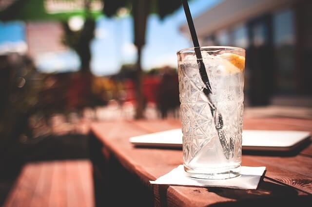 Providna čaša sa koktelom i slamčicom na šaknu na plaži